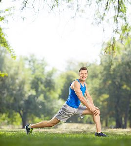 Young athlete stretching his legs in a park